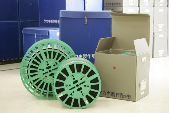 エンボスキャリアテープの製品と梱包材が並んでいる
